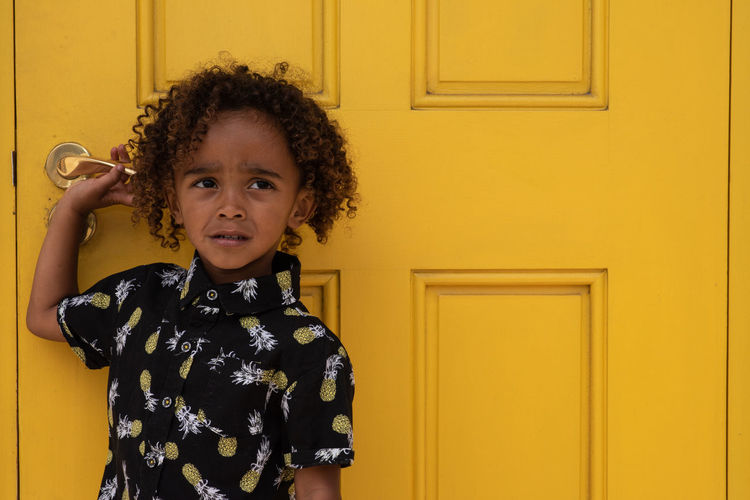 Yellow One Person Yellow Front View Standing Indoors  Lifestyles Real People Door Curly Hair Child Portrait Casual Clothing Waist Up Entrance Women Leisure Activity Holding Hairstyle Innocence Floral Pattern