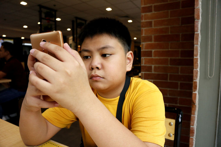 Boy using mobile phone while sitting in cafe