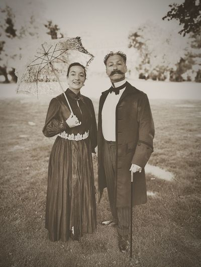 Portrait of well dressed couple standing on field