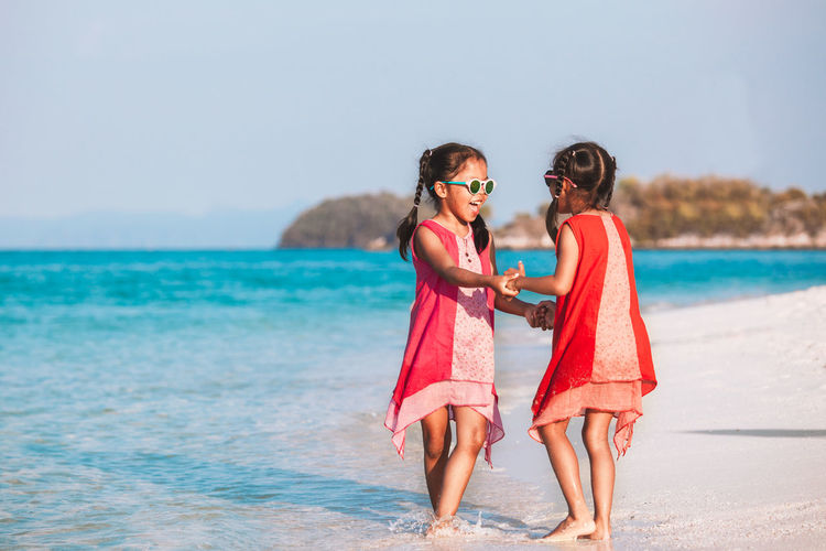 Girls playing while standing at beach