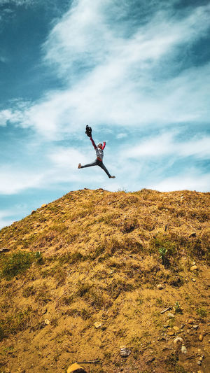 Man jumping against sky