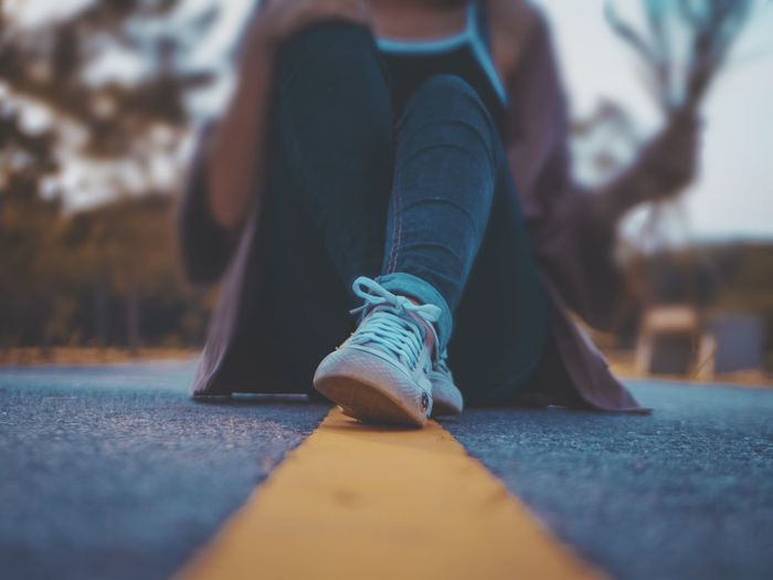 Low Section Of Woman Sitting On Road