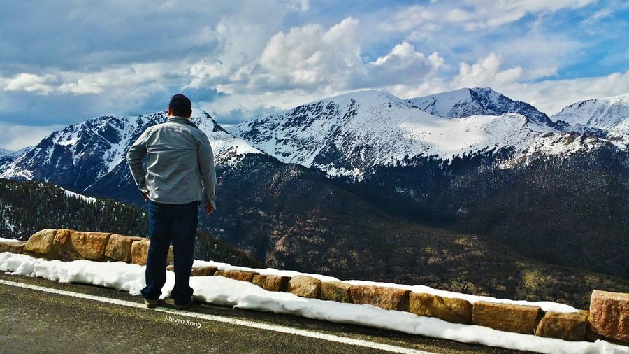 Full length rear view of man standing in front of snowcapped mountains at rocky mountain national park
