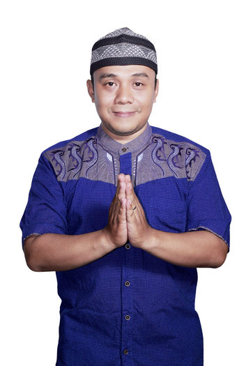 Portrait Smiling asian muslim man on white background Adult Blue Casual Clothing Cut Out Front View Looking At Camera One Person People Portrait Real People Smiling Standing Studio Shot Thumbs Up White Background Young Adult