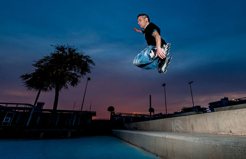 Man jumping steps on inline skates Architecture Full Length Jumping Leisure Activity Lifestyles Low Angle View Mid-air Motion Nature One Person Outdoors Plant Real People Side View Skill  Sky Sport Stunt Tree Vitality Young Adult