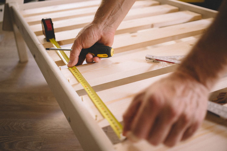 Cropped hands of man measuring wood at home