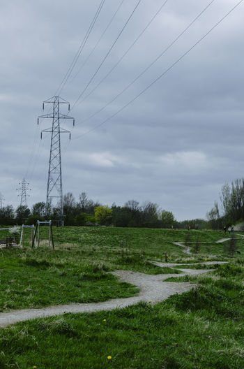 Plant Grass Electricity  Electricity Pylon Cable Landscape Technology Sky Field Land Environment Power Line  Power Supply Fuel And Power Generation Nature No People Tree Green Color Day Connection Outdoors Pylon Pylons Power Lines