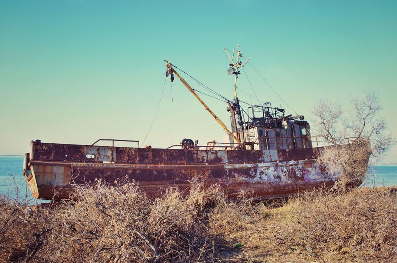 Abandoned ship on field against clear sky