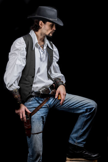 Handsome young man. This is an American cowboy. A vow to a white shirt, brown waistcoat and blue jeans. Black shoes on the feet. Carries a shtyapa, on a belt two pistols. The hair is of medium length; on the face is a beard and mustache. Authentic photo. Culture of America. Cowboy Wild West America American Gun National Authentic Moments Lifestyles Lifestyle One Person Candid Authentic Three Quarter Length Clothing Young Adult Hat Black Background Young Men Front View Real People Jeans Looking Men Holding Looking Away