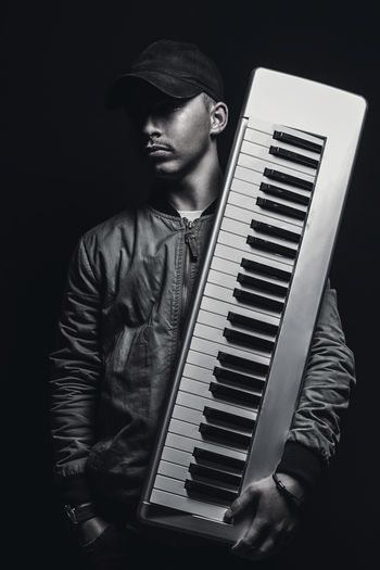 Musician Holding Synthesizer While Standing Against Black Background