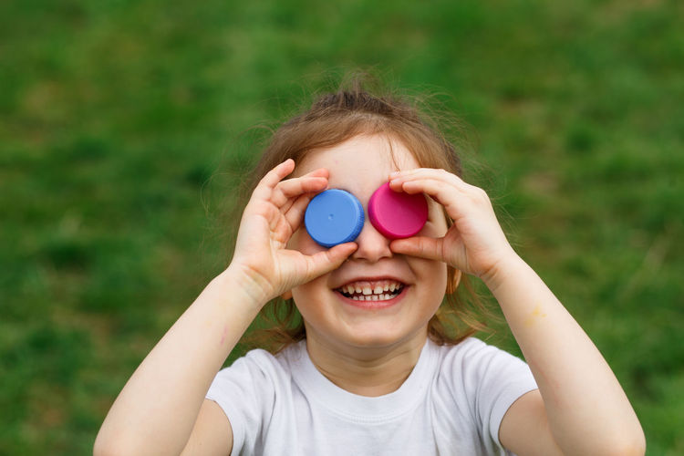 Close-up of smiling girl holding bottle caps on eyes