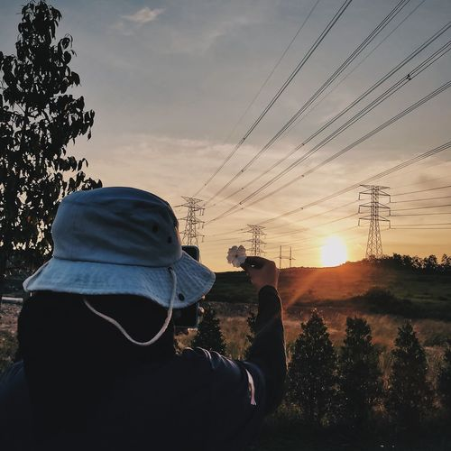 Rear view of woman holding flower against sky during sunset