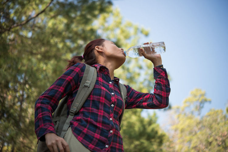 Low angle view of woman drinking water against sky