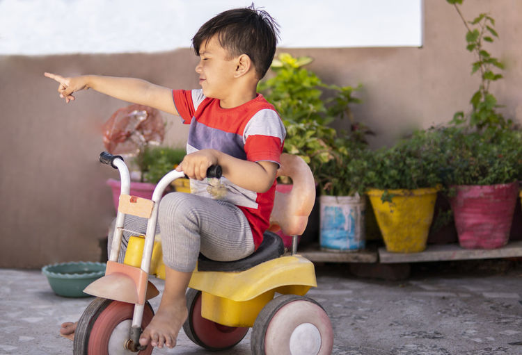 Boy playing with toy sitting outdoors