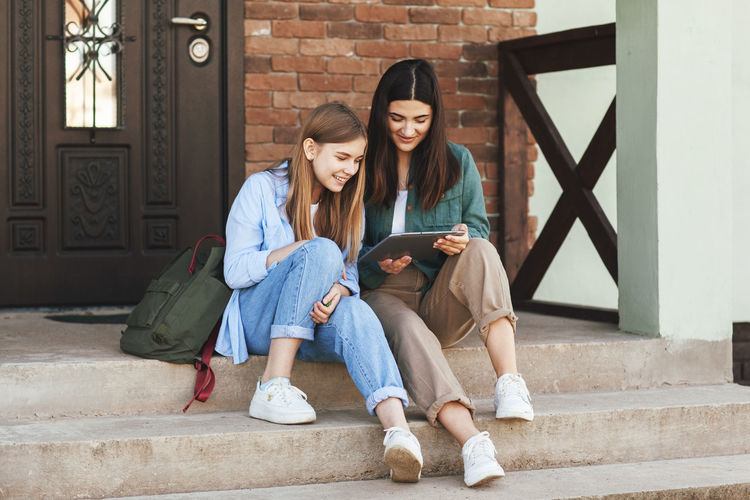 On the steps near the house, two beautiful girls-sisters who have come from the university