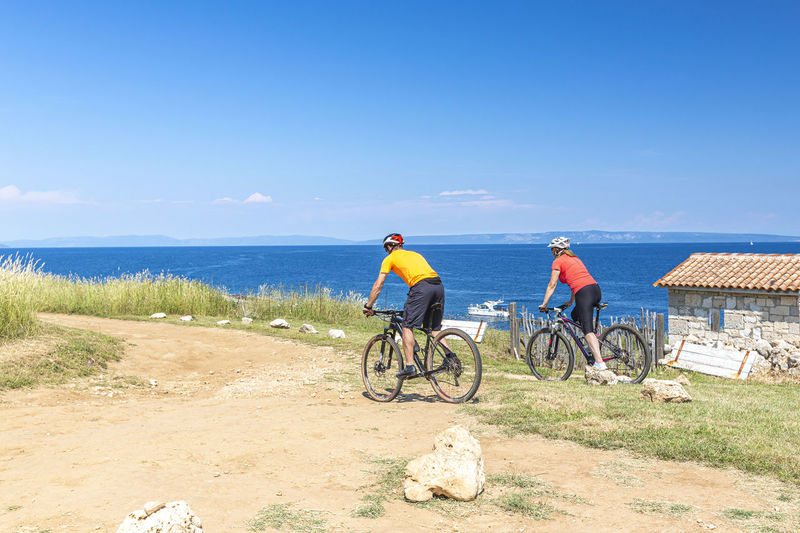 People riding bicycle by sea against sky
