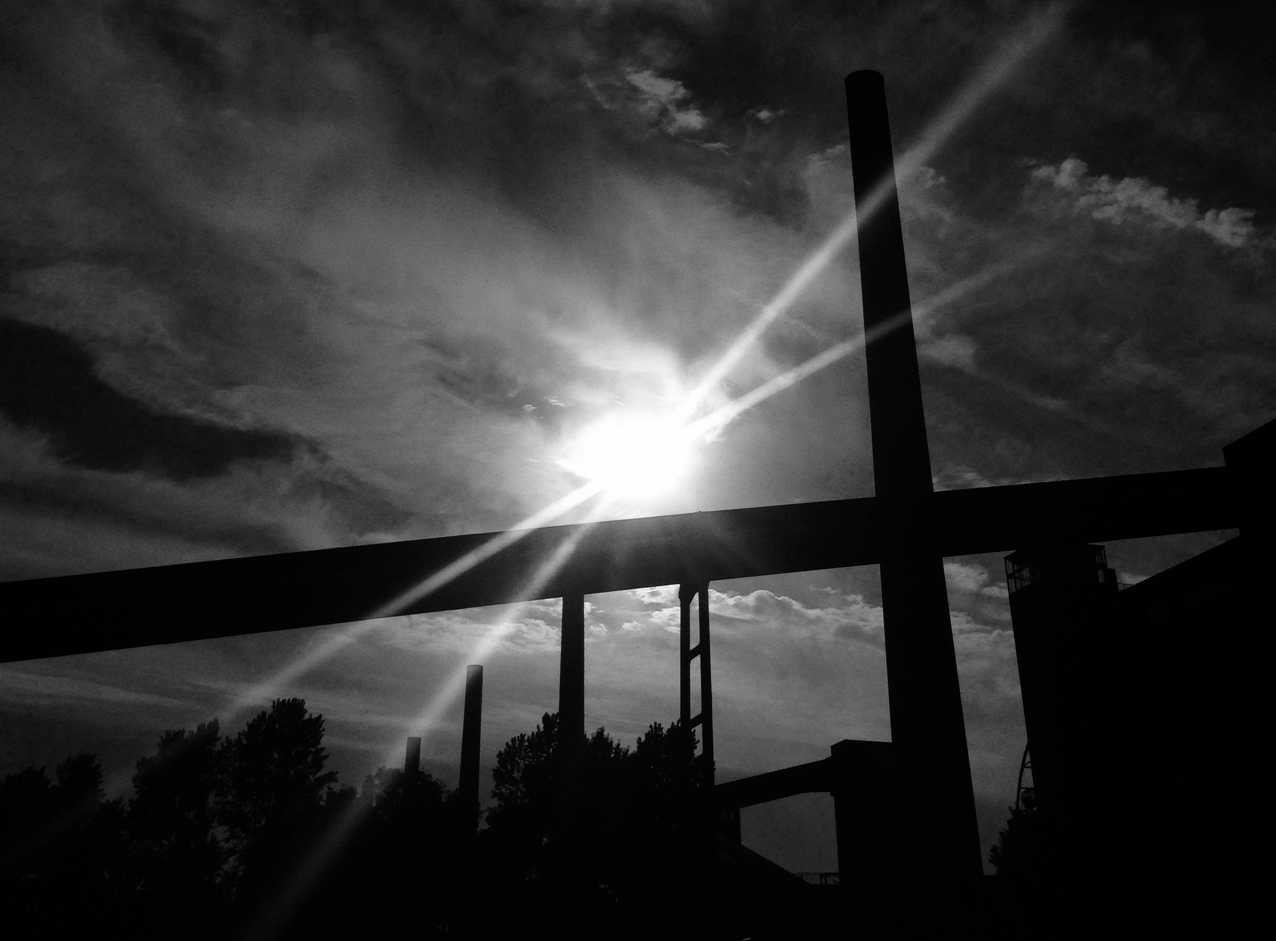 low angle view, sky, sun, built structure, architecture, silhouette, cloud - sky, sunbeam, sunlight, cloudy, cloud, lens flare, tree, connection, no people, nature, bridge - man made structure, outdoors, day, building exterior