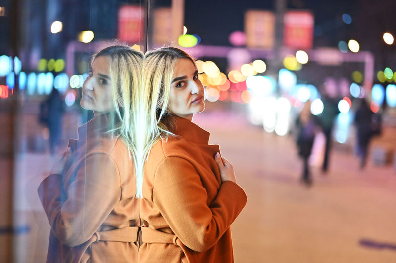 Woman standing by illuminated street at night