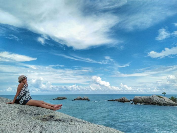 Woman sitting by sea against sky