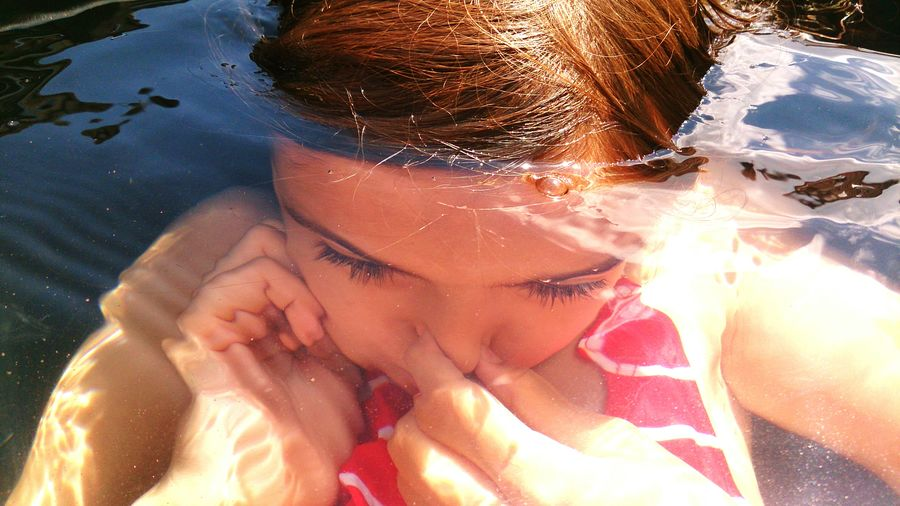 High angle view of girl holding breath while swimming