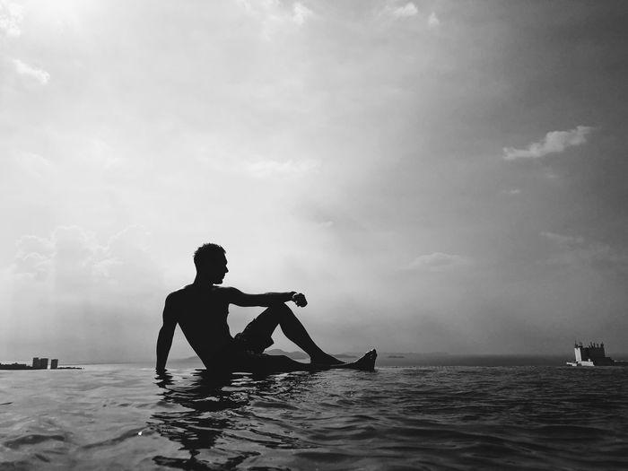 Silhouette man on sea against sky