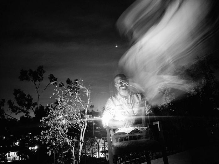 Long exposure image of man smoking cigarette against sky at night