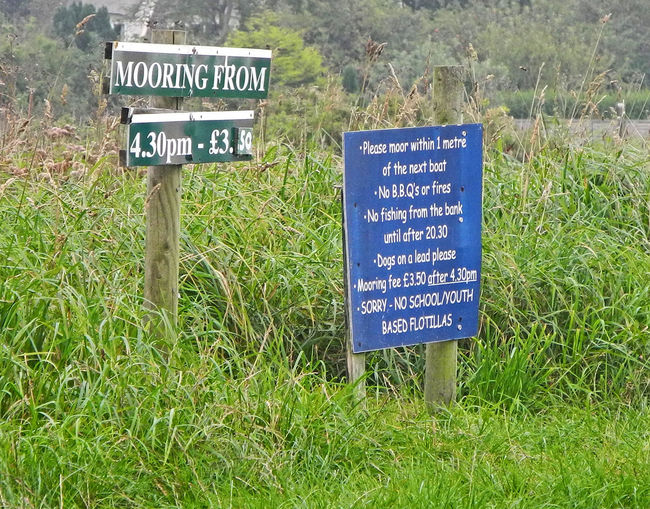 Moorings signs on the Norfolk Broads - UK Mooring Signs Boat Moorings Boating In The UK Close-up Communication Day Field Grass Green Color Nature No People Outdoors Placard Signboard Text Western Script