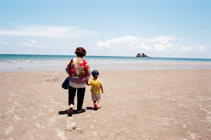 Rear View Of Grandmother And Grandson Walking At Beach Against Sky