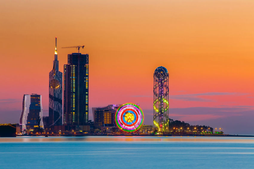 Batumi, Adjara, Georgia. Scene Of Resort Town At Sunset Or Sunrise. Bright Evening Sky. View From Sea Beach To Illuminated Cityscape With Modern Urban Architecture, Skyscrapers And Tower. Golden Hour Batumi Bright Colour Your Horizn Dramatic Sky Georgia Orange Pink Travel Adjara Architecture City Dusk Illuminated Landmark Night Outdoors Sea Sky Skyscraper Sunset Tourism Tower Urban Water Yellow The Traveler - 2018 EyeEm Awards My Best Travel Photo