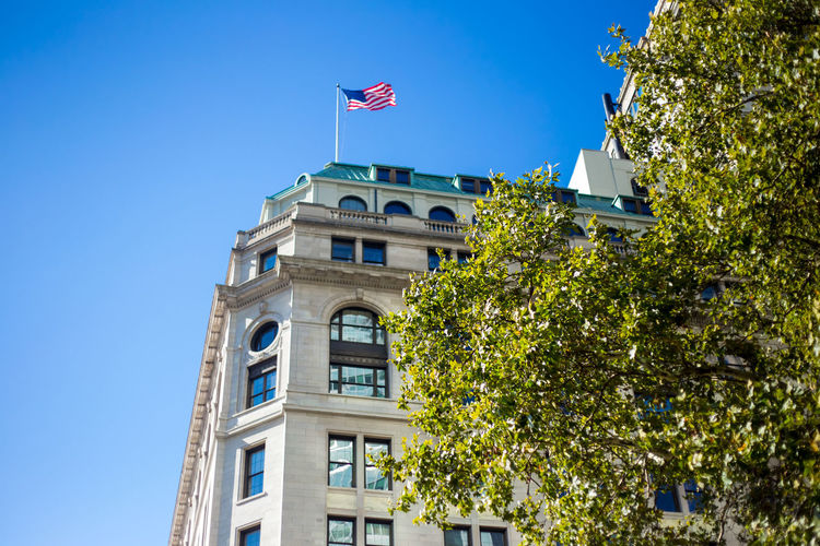 Low Angle View Of American Flag Waving On Building Terrace