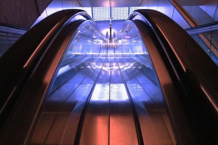Illuminated reflection on escalator railing