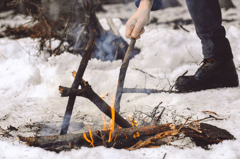 Low section of man burning campfire during winter