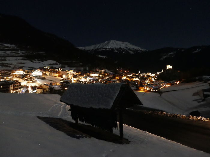 High angle view of illuminated houses by snowcapped mountains at night