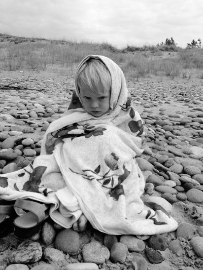 Boy covered with shawl sitting on pebbles at beach
