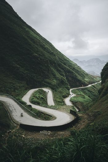 Scenic view of winding road on mountain against sky