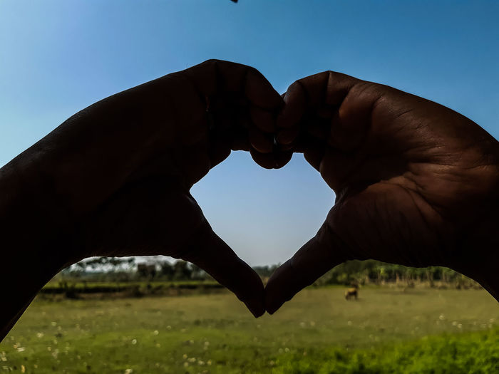 Person hand holding heart shape against clear sky