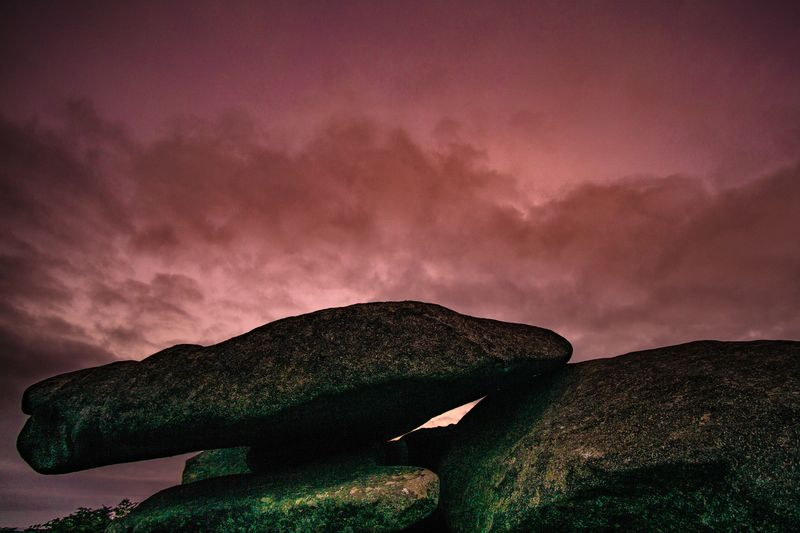 Low angle view of rock against sky at sunset