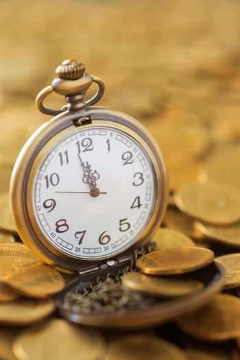 Close-up of pocket watch on gold coins at table