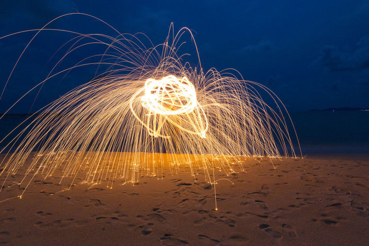 Illuminated Light Painting Over Sand At Beach Against Sky During Night