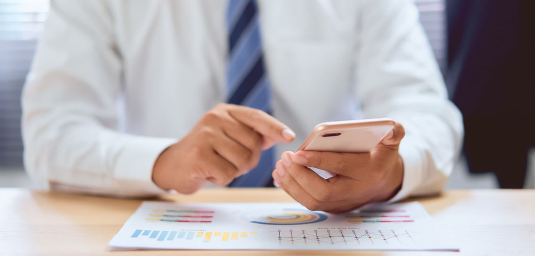 Midsection of man using smart phone on table