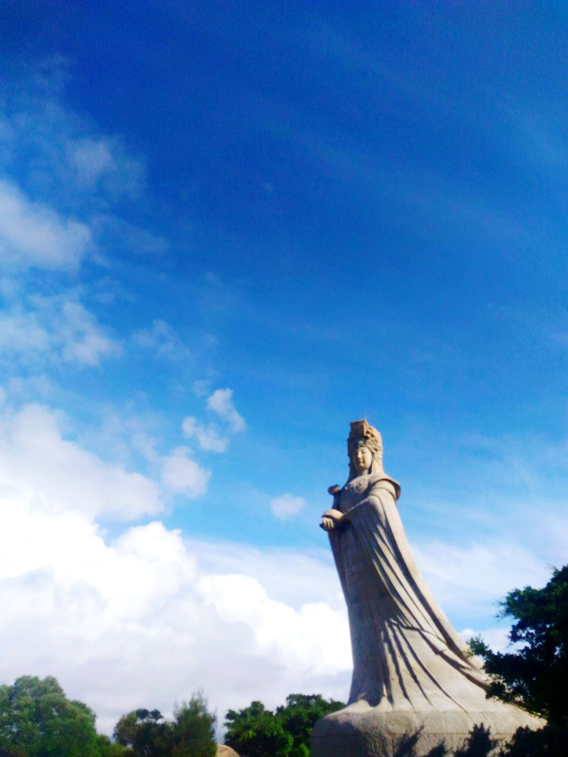 statue, sculpture, human representation, blue, art and craft, low angle view, sky, art, cloud - sky, cloud, day, outdoors, monument, creativity, memories, pedestal, no people, history