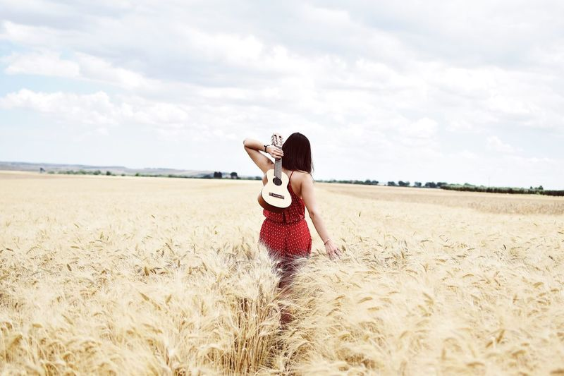 Young woman with ukulele on field against sky