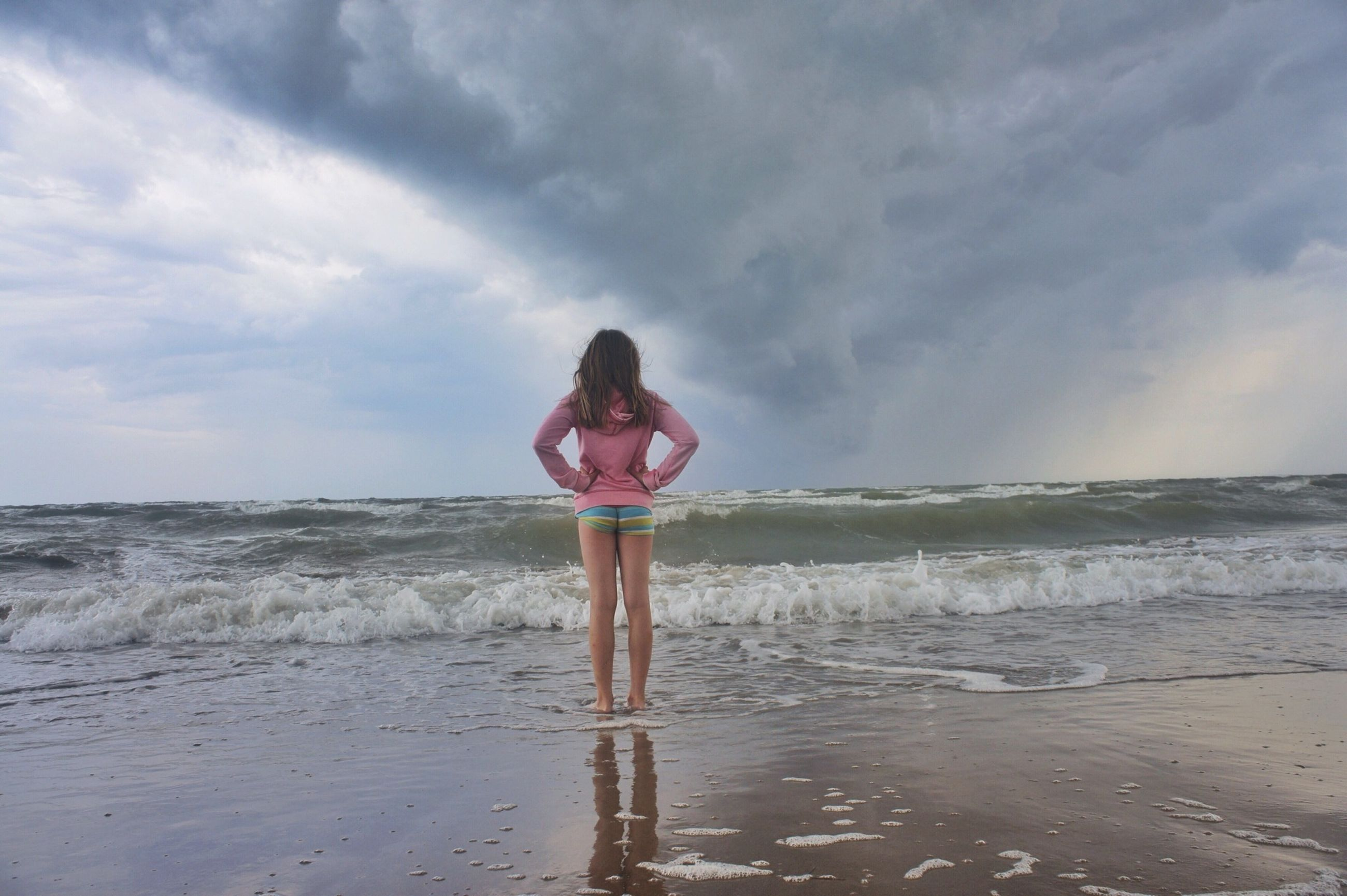 water, sky, full length, standing, sea, lifestyles, leisure activity, beach, cloud - sky, horizon over water, tranquility, casual clothing, tranquil scene, shore, scenics, nature, rear view, beauty in nature