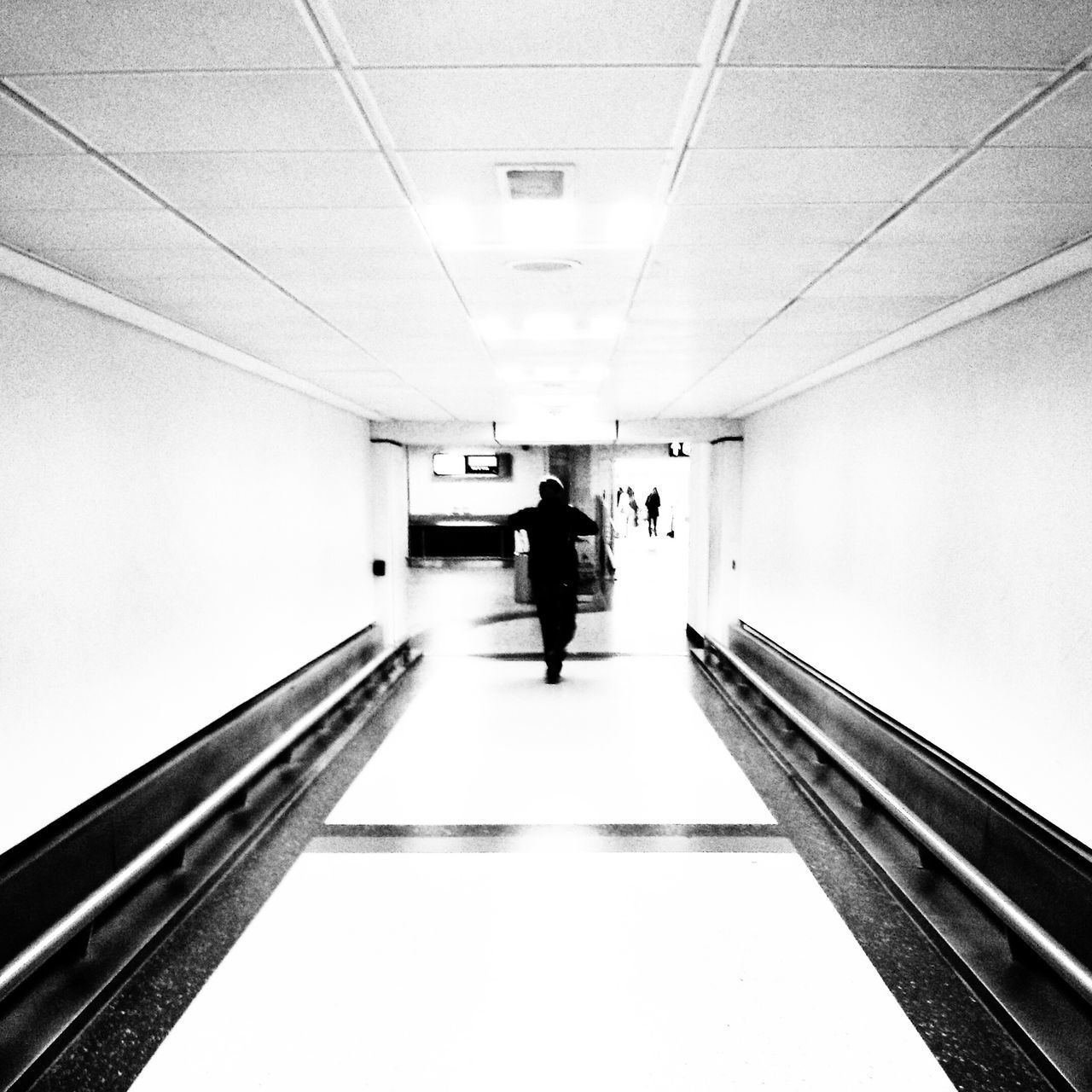 REAR VIEW OF MAN STANDING ON ESCALATOR IN ILLUMINATED UNDERGROUND