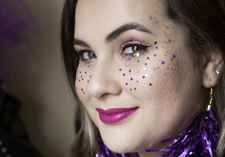 Close-up portrait of woman with confetti on face