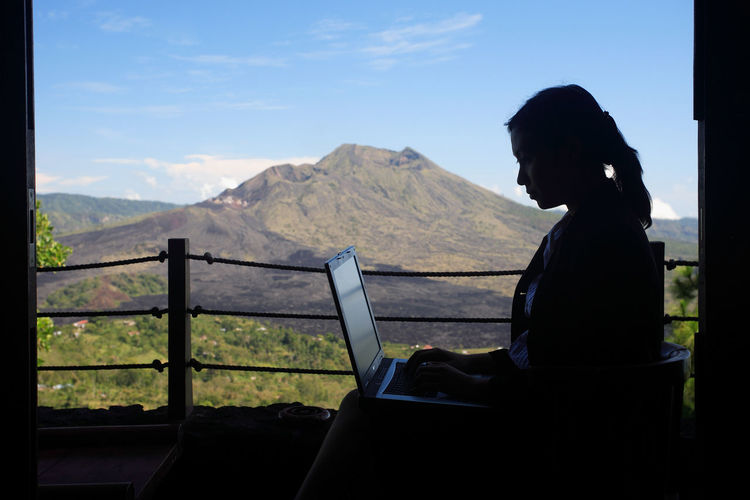 Side View Of Woman Using Laptop Against Mountain