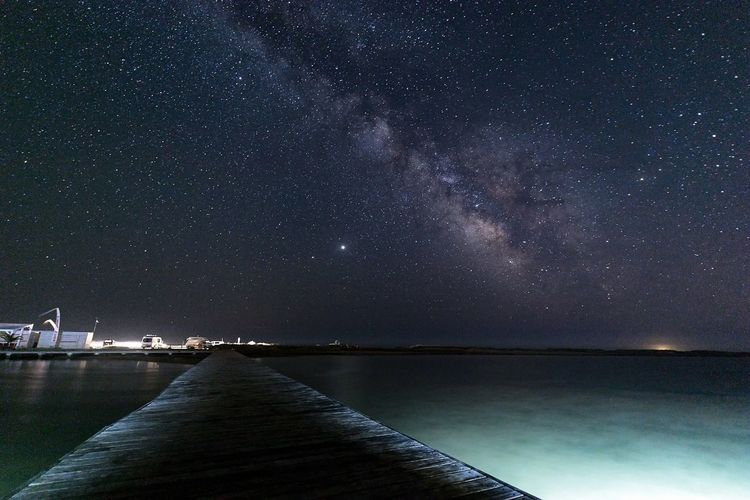 Scenic view of sea against sky at night with the milkyway