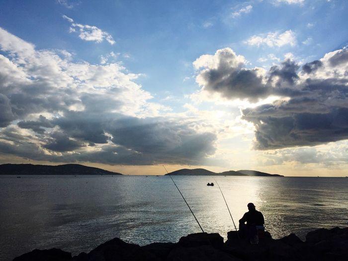 Silhouette man fishing at beach against sky