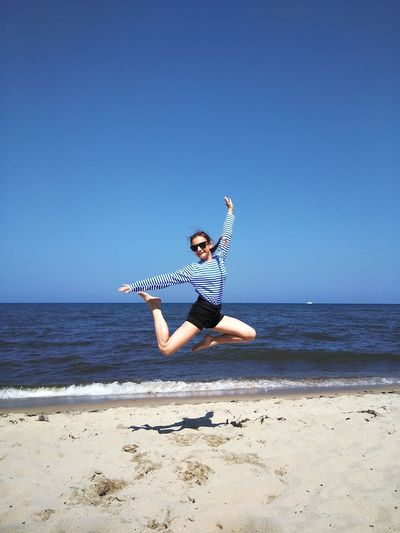 Portrait of teenage girl jumping at beach against clear blue sky