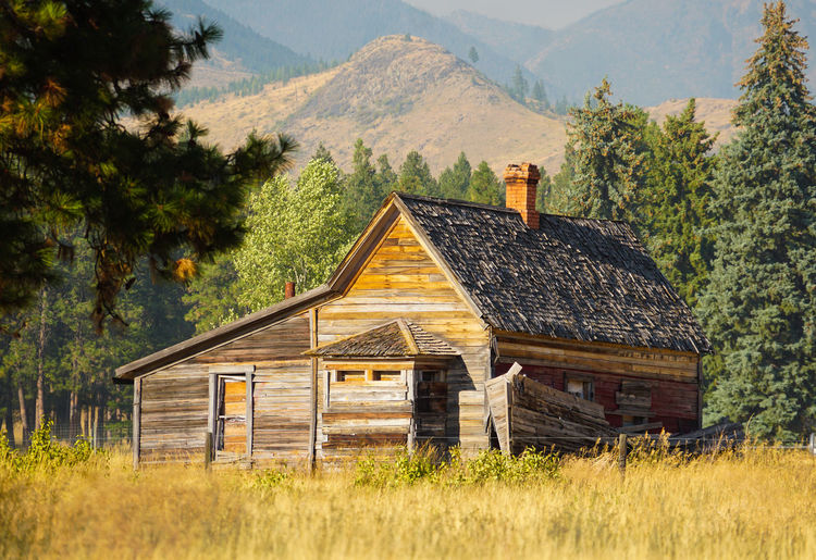 Abandoned house on field against mountain